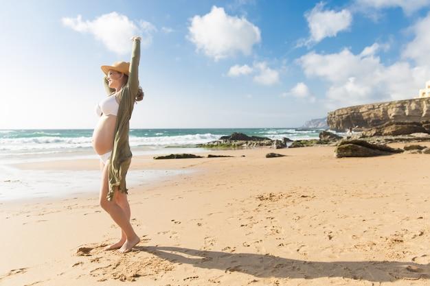 Porträt der lächelnden schwangeren frau, die arm ausdehnt
