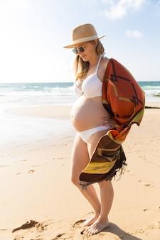 Porträt der lächelnden schwangeren frau, die auf sand schaut
