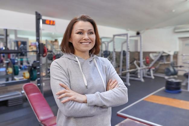 Porträt der lächelnden selbstbewussten frau mittleren alters mit gefalteten händen im fitnessstudio