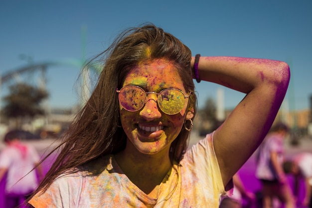 Porträt der lächelnden tragenden sonnenbrille der jungen frau bedeckt mit holi farbe