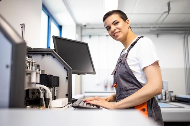 Porträt der lächelnden weiblichen arbeitskraft, die industrielle produktionsmaschine bereitsteht.