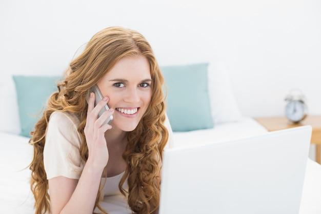 Porträt der lächelnden zufälligen frau, die laptop und mobiltelefon im bett verwendet