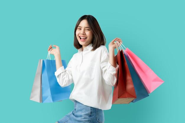 Porträt der lächelnden zufälligen kleidung der asiatischen frau der junge, die mehrfarbige einkaufstaschen auf hellblauem hält