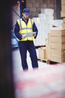 Porträt der lagerarbeitskraft mit klemmbrett im lager
