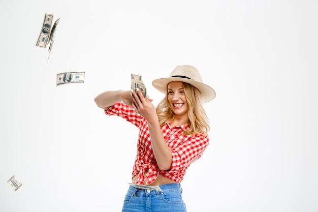 Porträt der landfrau, die geld auf weiß wirft.