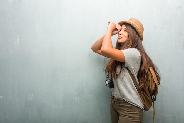 Porträt der lateinischen frau des jungen reisenden gegen eine wand, die durch einen abstand schaut, sich versteckt und schielt