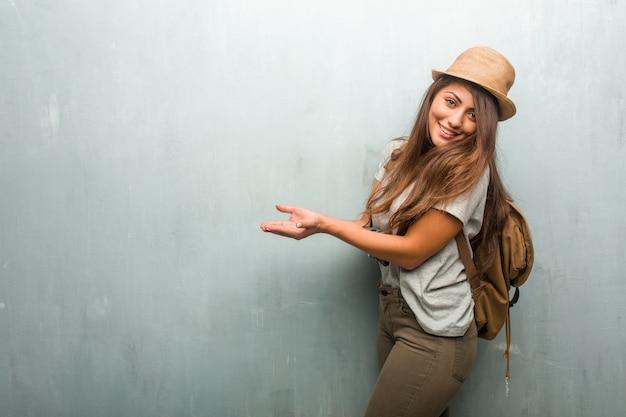 Porträt der lateinischen frau des jungen reisenden gegen eine wand, die etwas mit den händen hält