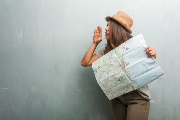 Porträt der lateinischen frau des jungen reisenden gegen eine wand, die klatschuntergehenflüstern flüstert