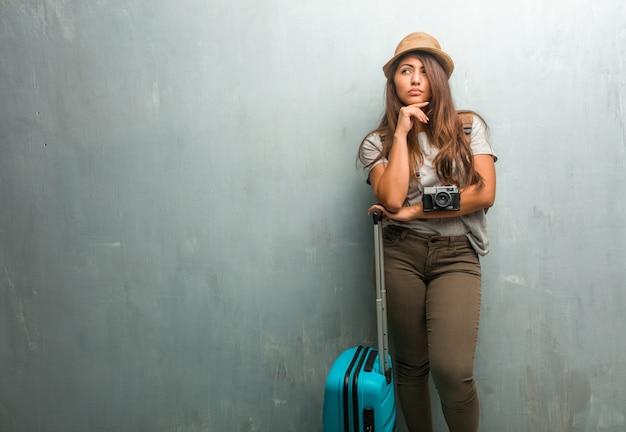 Porträt der lateinischen frau des jungen reisenden gegen eine wand, die oben denkt und schaut