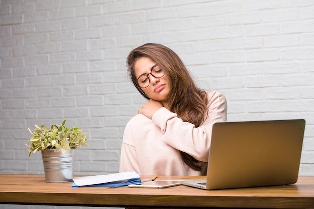 Porträt der lateinischen frau des jungen studenten, die auf ihrem schreibtisch mit den rückseitigen schmerz wegen des arbeitsstresses sitzt