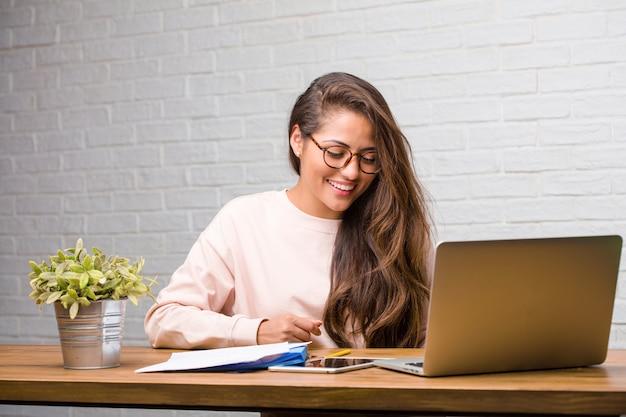 Porträt der lateinischen frau des jungen studenten, die auf ihrem schreibtisch sitzt und lacht und spaß hat, entspannt und nett ist, fühlt sich überzeugt und erfolgreich