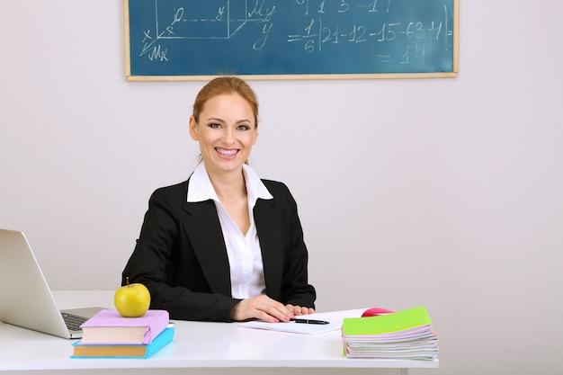 Porträt der lehrerin, die im klassenzimmer arbeitet