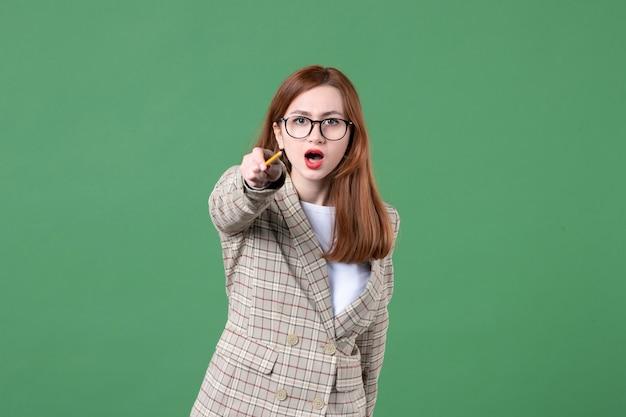 Porträt der lehrerin, die mit bleistift auf grün zeigt