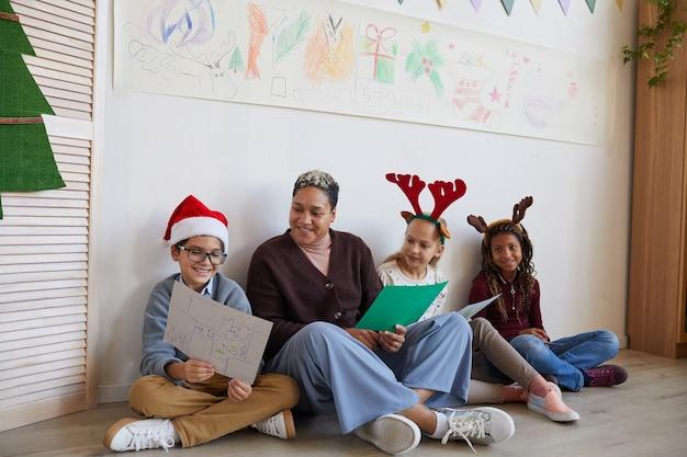Porträt der lehrerin in voller länge, die auf boden mit multiethnischer gruppe von kindern sitzt, die bilder halten, während kunstunterricht an weihnachten genießen, raum kopieren