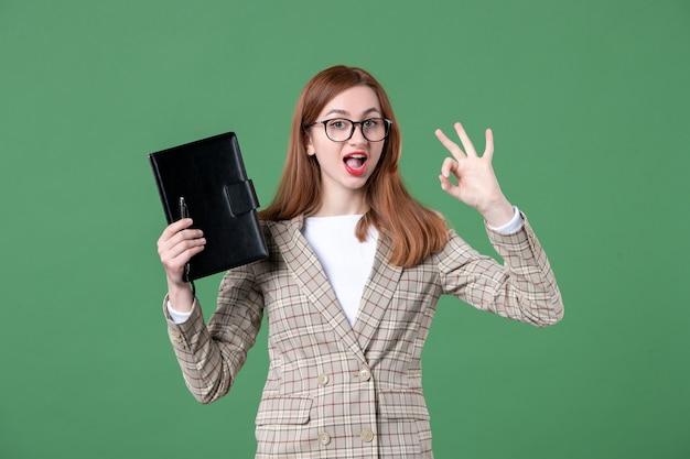 Porträt der lehrerin mit notizblock auf grün