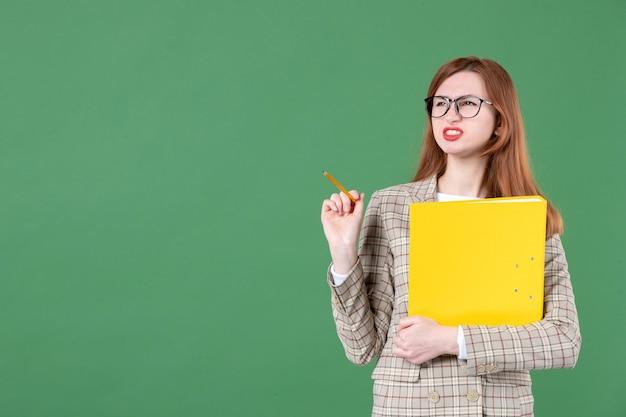 Porträt der lehrerin posiert mit gelber datei und bleistift auf grün