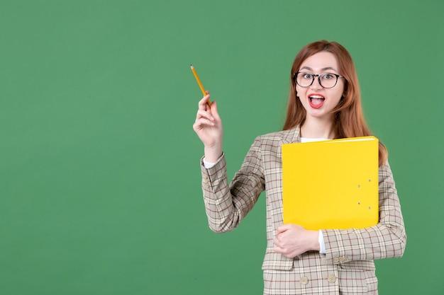 Porträt der lehrerin posiert mit gelber datei und bleistift glücklich auf grün