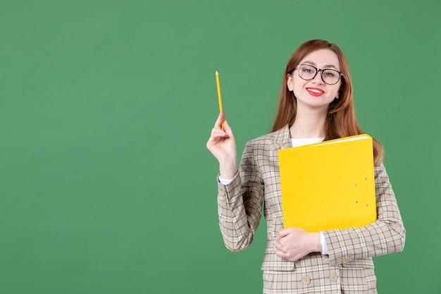 Porträt der lehrerin posiert mit gelber datei und bleistift lächelnd auf grün