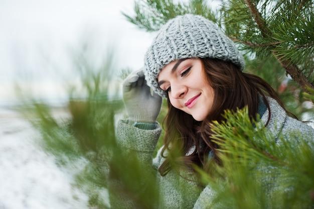 Porträt der leichten frau im grauen mantel und im hut gegen den weihnachtsbaum im freien.