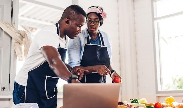Porträt der liebe afroamerikanisches paar, das spaß hat, zusammen zu kochen und nach rezept im internet mit laptop-computer zu suchen, um das leckere essen in der küche zu hause vorzubereiten