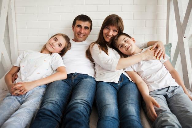 Porträt der liebevollen familie liegend auf dem bett, das kamera im schlafzimmer betrachtet