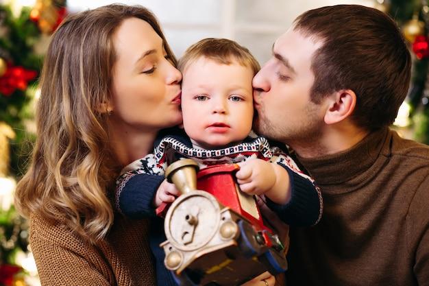 Porträt der liebevollen glücklichen eltern, die ihren sohn in den wangen küssen, die spielzeugzug als geschenk für weihnachten halten