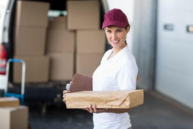 Porträt der lieferfrau, die ein klemmbrett und ein paket hält