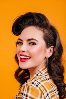 Porträt der lockigen brünetten frau mit charmantem lächeln. studioaufnahme des glückseligen pinup-mädchens, das auf gelbem hintergrund lacht.