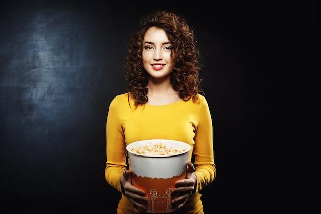 Porträt der lockigen frau, die popcorn-eimer hält, der gerade schaut