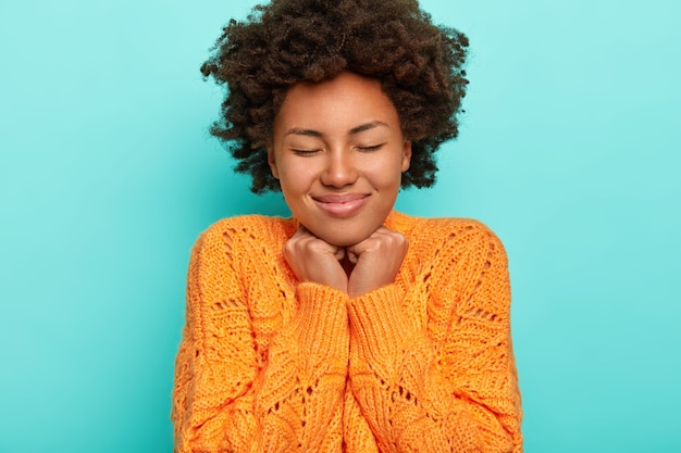Porträt der lockigen frau mit knackigem haar, hält hände unter kinn, fühlt vergnügen, trägt gestrickten orange pullover, isoliert über blauem hintergrund
