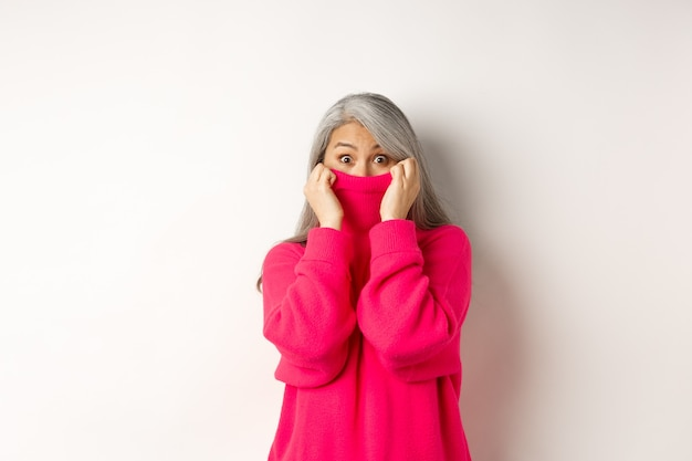 Porträt der lustigen asiatischen großmutter, die das gesicht im pulloverkragen versteckt, in die kamera albern späht und auf weißem hintergrund steht