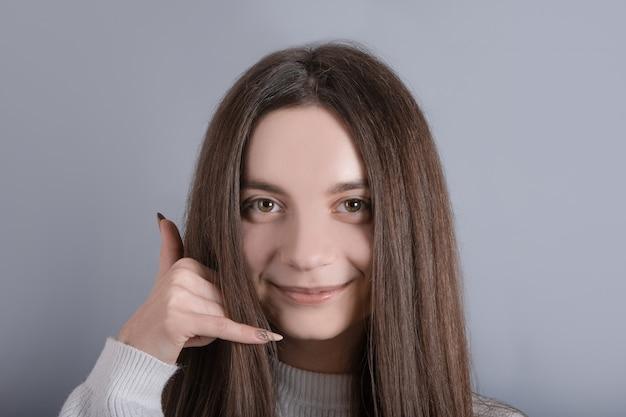 Porträt der lustigen entzückenden jungen dame frau mädchen tragen pullover zeigt uns einen anruf mich zeichen telefon