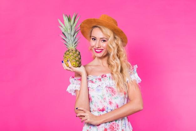 Porträt der lustigen frau und der ananas über rosa hintergrund. konzept für sommer, ernährung und gesunden lebensstil.