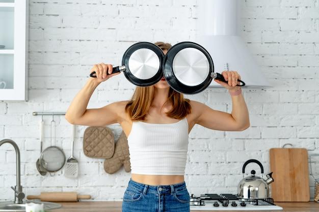 Porträt der lustigen hausfrau mit küchengeräten