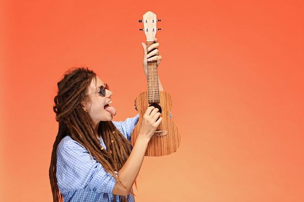 Porträt der lustigen jungen frau, die ukulele auf orangem hintergrund spielt