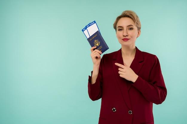 Porträt der lustigen jungen frau mit pass und bordkarte auf blauem hintergrund. grenzen öffnen. beginn des flugverkehrs nach einer pandemie.