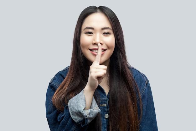 Porträt der lustigen schönen brünetten asiatischen jungen frau in der zufälligen blauen jacke mit dem make-up, das mit dem schweigenzeichenfinger auf den lippen steht und geheimnis erzählt. studioaufnahme, auf hellgrauem hintergrund isoliert.