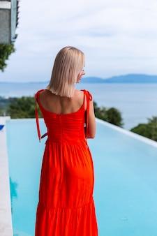 Porträt der luxus aussehenden frau im roten orange abendkleid im reichen hotel