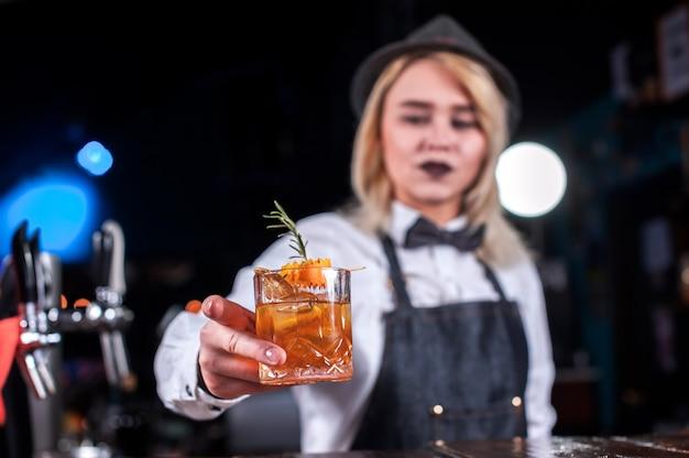 Porträt der mädchenbardame macht eine show, die einen cocktail kreiert