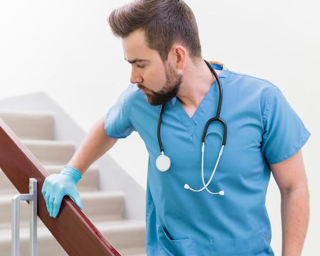 Porträt der männlichen krankenschwester, die chirurgische handschuhe trägt