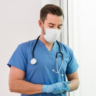 Porträt der männlichen krankenschwester, die handschuhe und maske trägt