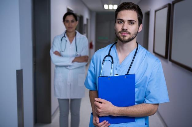 Porträt der männlichen krankenschwester, die mit doktor im hintergrund steht
