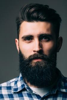 Porträt der männlichkeit. porträt des schönen jungen bärtigen mannes beim stehen gegen graue wand