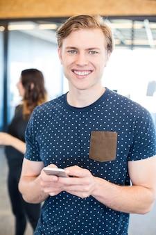 Porträt der mannversenden von sms-nachrichten auf smartphone im büro