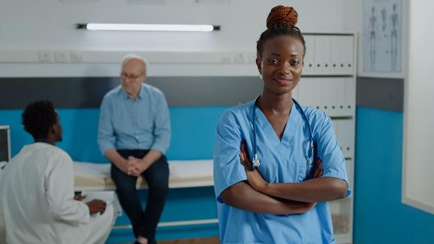 Porträt der medizinischen krankenschwester, die kamera im kabinett betrachtet