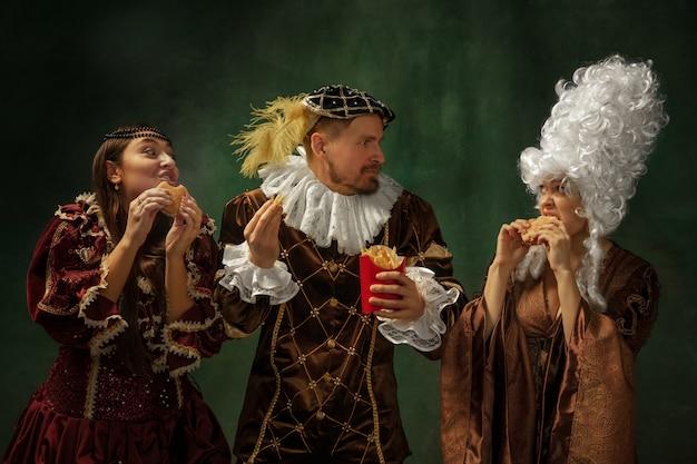 Porträt der mittelalterlichen jungen leute in der weinlesekleidung an der dunklen wand