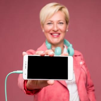 Porträt der mittleren greisin smartphoneschablone zeigend