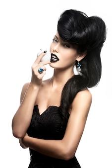 Porträt der modefrau mit moderner frisur und lippen in der schwarzen farbe mit weißem apfel
