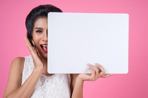 Porträt der modefrau weiße fahne anzeigend