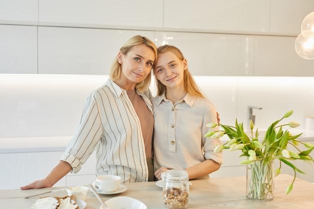 Porträt der modernen erwachsenen mutter, die mit jugendlicher tochter im kücheninnenraum beim gemeinsamen frühstück aufwirft